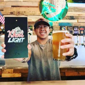 Khoi Holding Khoi's Light Sign & Beer